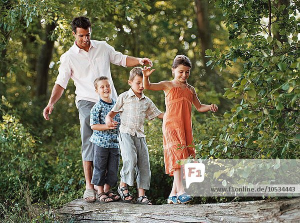 Children and father walking on a log