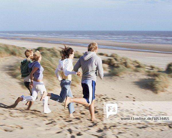 Gruppe von Freunden  die am Strand laufen