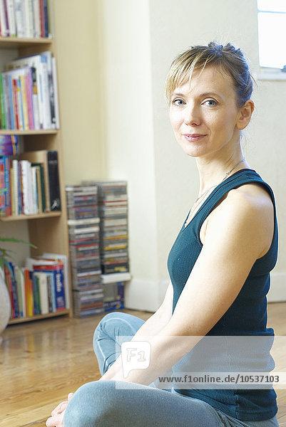 Frau beim Sport zu Hause sitzend