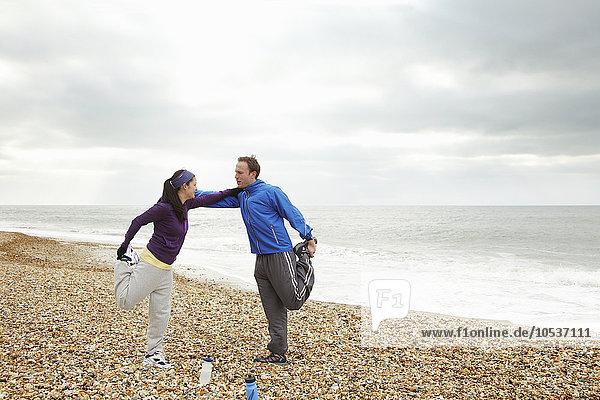 Paar Stretching am Strand bei bewölktem Himmel