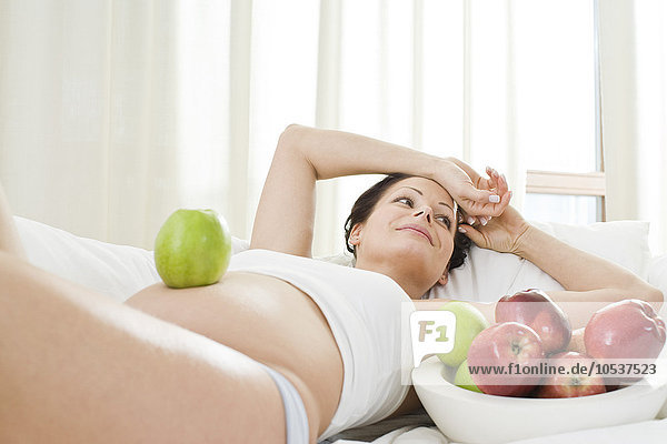 pregnant woman eating apples