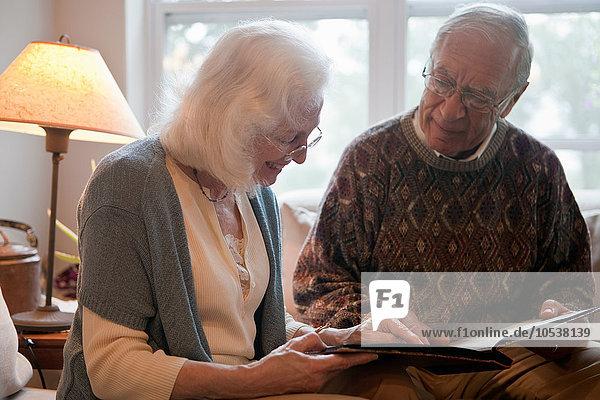 Seniorenpaar beim Durchblättern des Fotoalbums
