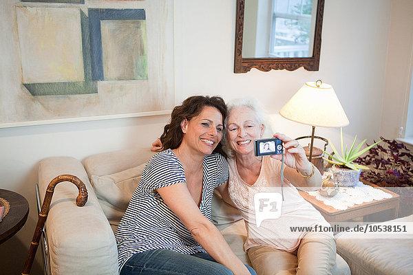 Seniorin und Tochter beim Selbstporträt zu Hause