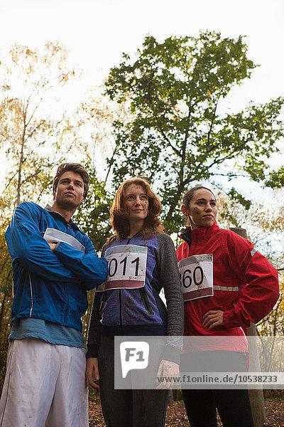 Junge Freunde in Sportbekleidung stehen zusammen im Wald