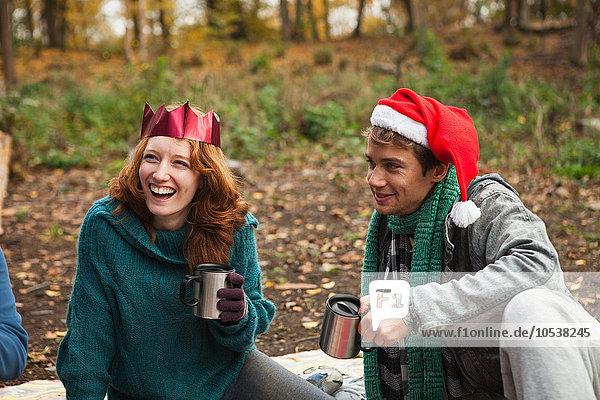 Junges Paar mit Weihnachtsmützen und Kronen im Wald