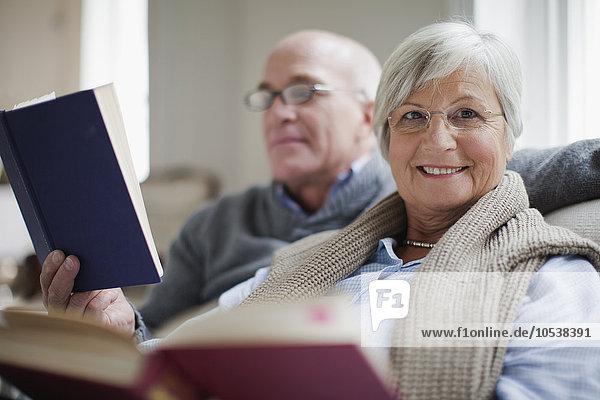 Lächelndes älteres Paar beim Lesen von Büchern