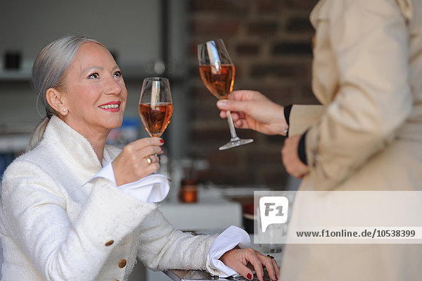 Older women toasting each other in cafe
