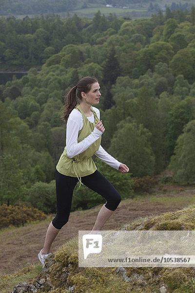 Frau klettert auf ländlichen Hügel