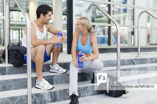 Ein Paar redet auf Turnhallenstufen