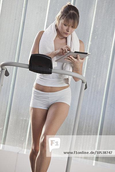 Frau mit Tablet-Computer im Training