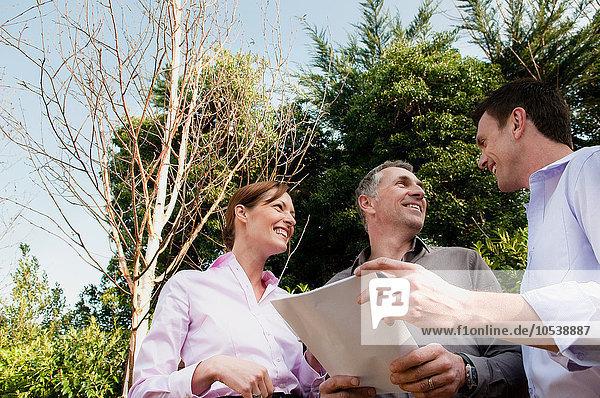 Drei Geschäftsleute mit Dokument