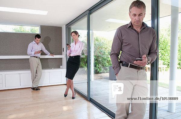 Drei Geschäftsleute SMS an Handys im Home-Office