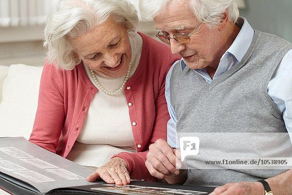 Seniorenpaar beim Betrachten des Fotoalbums