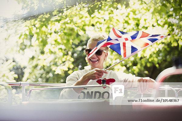 Lächelnde Frau mit britischer Flagge im Doppeldeckerbus
