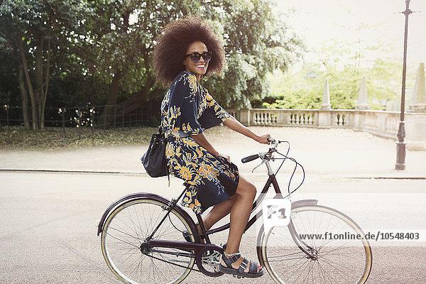 Portrait lächelnde Frau mit Afrofahrrad im Stadtpark