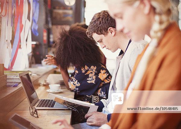 Menschen arbeiten und trinken Kaffee in einer Reihe im Cafe