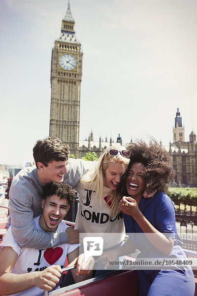 Enthusiastische Freunde im Doppeldeckerbus unter dem Big Ben-Uhrturm  London  Großbritannien