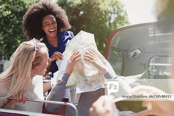 Verspielte Freunde mit Karte im Doppeldeckerbus