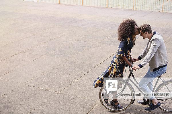 Zärtliche Frau  die den Mann auf dem Fahrrad küsst.