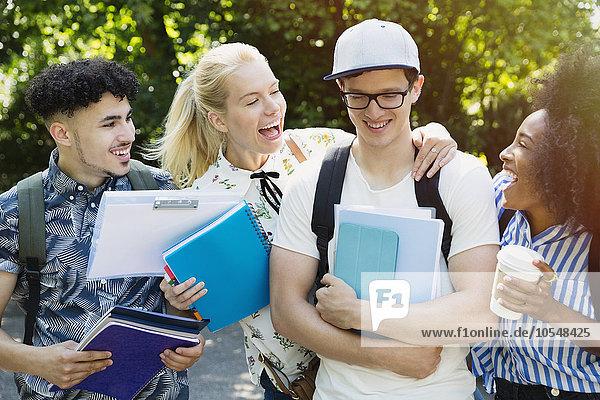 Enthusiastische Studenten scherzen mit Freunden draußen