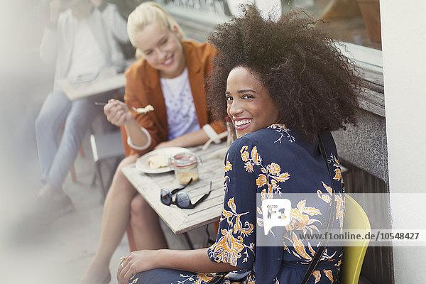 Porträt lächelnde Frau mit Freundin im Straßencafé