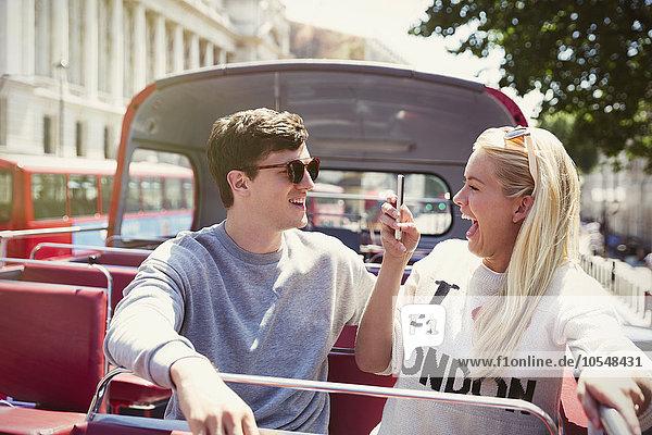 Enthusiastische Freundin fotografiert Freund im Doppeldeckerbus