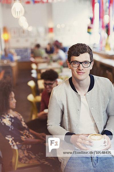 Portrait lächelnder Mann mit Brille trinkt Cappuccino im Cafe