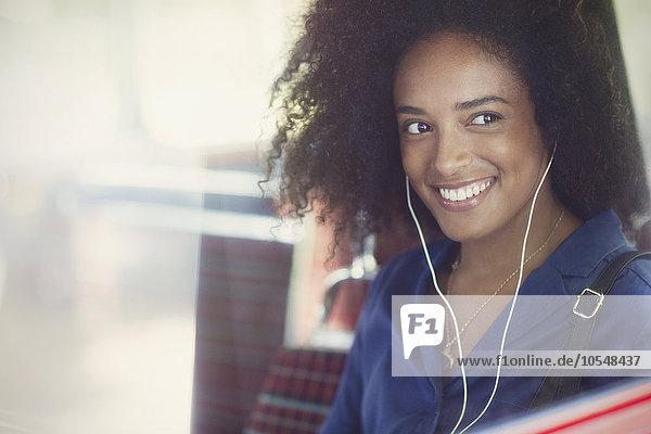 Lächelnde Frau mit Afro Musik hören mit Kopfhörer im Bus