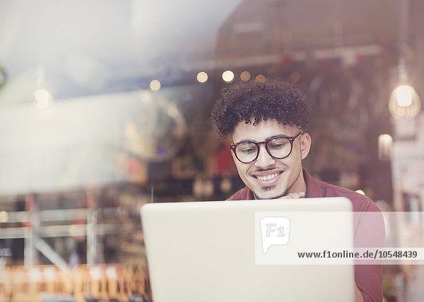 Lächelnder Mann mit lockigen schwarzen Haaren mit Laptop am Caféfenster