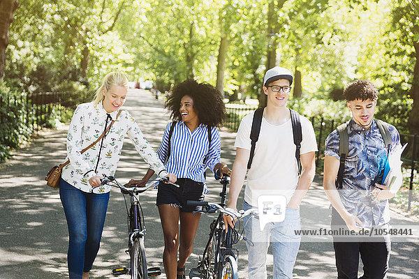 Freunde beim Wandern mit dem Fahrrad im Park