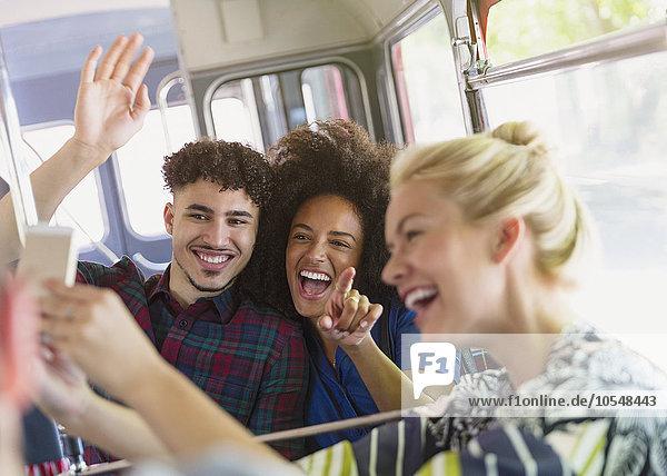 Enthusiastische Freunde nehmen Selfie mit in den Bus
