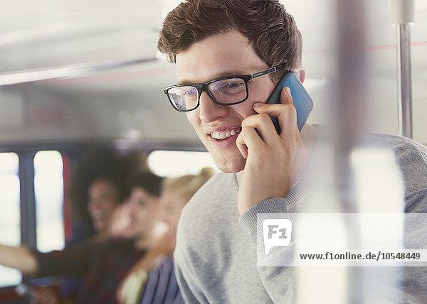 Lächelnder Mann mit Brille spricht auf dem Handy im Bus