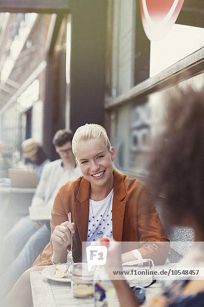 Lächelnde Freunde essen Dessert auf dem Bürgersteig Cafe