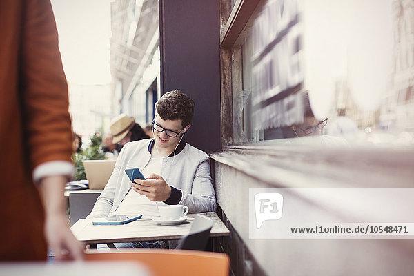 Mann hört Kopfhörer mit mp3-Player auf dem Bürgersteig Cafe