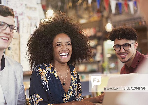 Lachende Freunde mit Laptop im Cafe