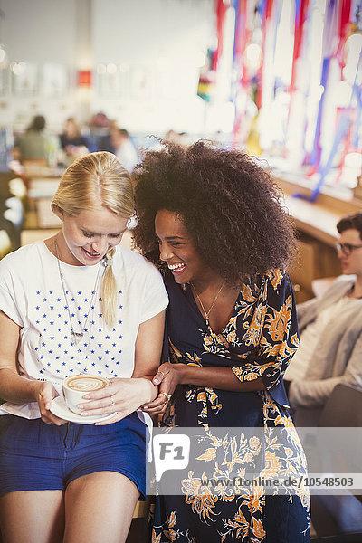Freunde lachen und trinken Cappuccino im Cafe