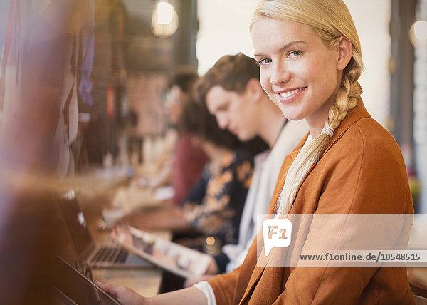 Portrait lächelnde blonde Frau mit digitalem Tablett im Cafe