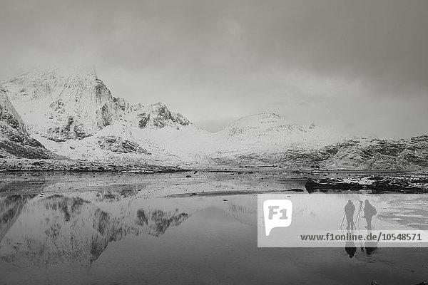 Fotografen unter schneebedeckten Bergen und ruhiger Bucht  Norwegen