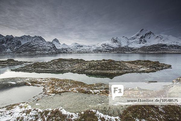 Schneebedeckte Bergkette hinter zerklüfteter Bucht  Sund  Lofoten Inseln  Norwegen