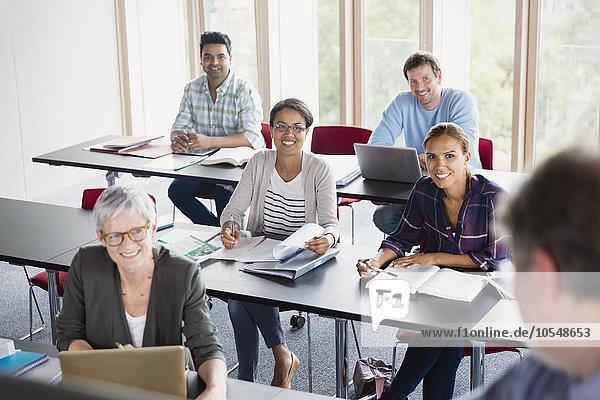 Lächelnde Schüler beobachten Lehrer in der Erwachsenenbildung