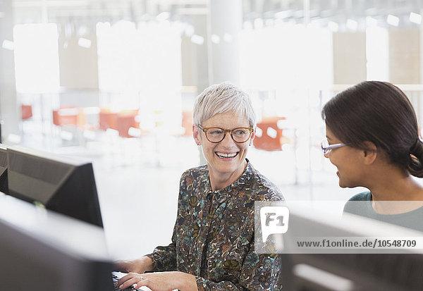 Lächelnde Frauen beim Sprechen am Computer in der Erwachsenenbildung