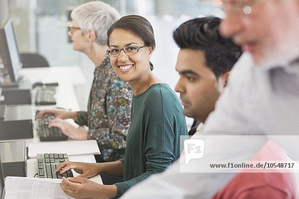 Portrait lächelnde Frau am Computer im Klassenzimmer der Erwachsenenbildung