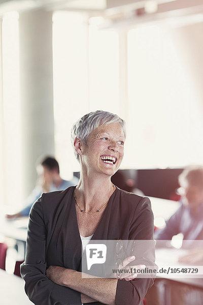 Lachende Seniorin im Klassenzimmer der Erwachsenenbildung