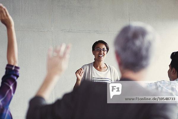 Lehrer ruft Schüler mit erhobenen Händen im Klassenzimmer der Erwachsenenbildung an