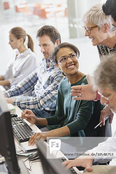 Schüler sprechen am Computer im Klassenzimmer der Erwachsenenbildung