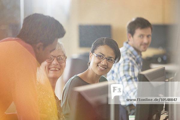 Lächelnde Schüler beim Sprechen an Computern in der Erwachsenenbildung