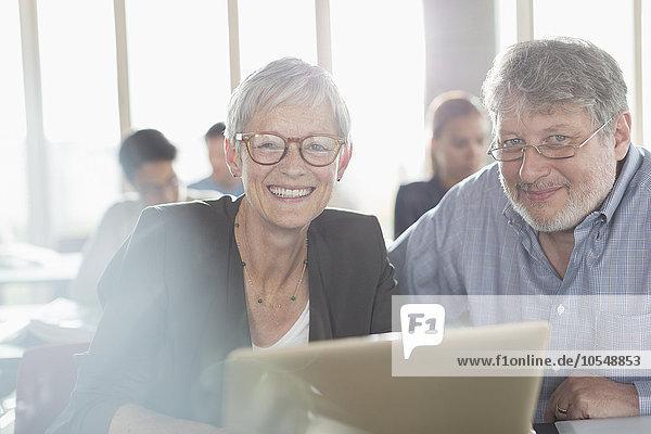 Portrait selbstbewusste Seniorin am Laptop in der Erwachsenenbildung