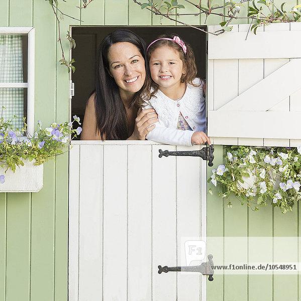 Portrait lächelnde Mutter und Tochter im Spielhausfenster