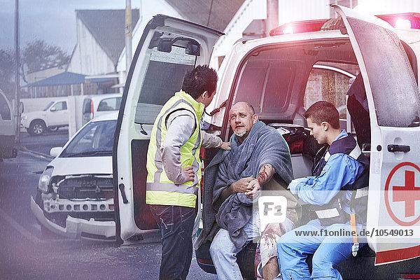 Rettungskräfte  die das Opfer eines Autounfalls auf der Rückseite des Rettungswagens betreuen.