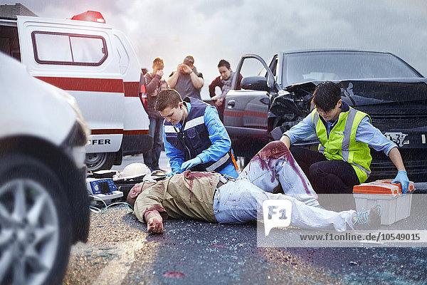 Rettungskräfte neigen zu blutigen Autounfallopfern auf der Straße